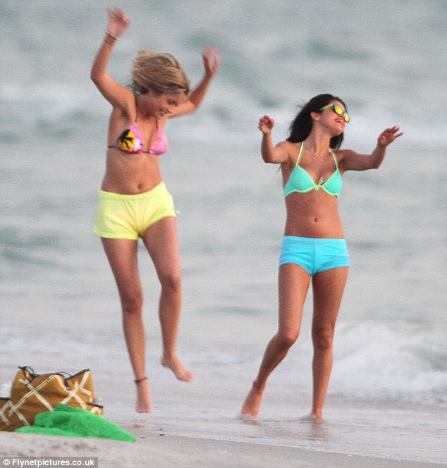 Life's a beach: Ashley Benson and Selena lark about in their bikinis