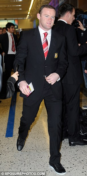 On board: Wayne Rooney arrives at Manchester Airport for United's trip to Bilbao