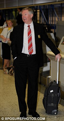 Keeping guard: Manchester United manager Sir Alex Ferguson stands by his suitcase