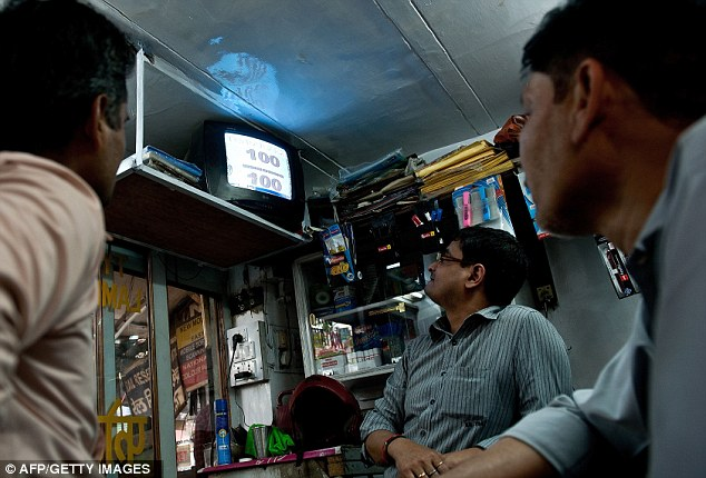 Eyes on the screen: Indian fans watch Tendulkar's century on a television at a shop in New Delhi