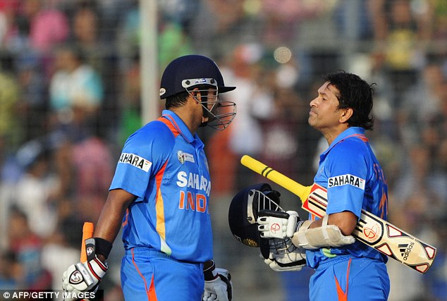 Well done: Team-mate Suresh Raina congratulates Tendulkar on his achievement