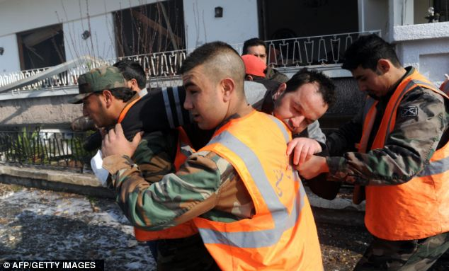 Casualties: Rescue workers carry an injured man after the bombs wounded and killed police and civilians