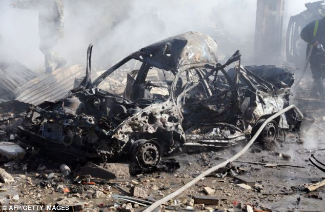 Nascent civil war: Vehicles were left as hunks of twisted metal after the attacks, which apparently targeted the capital's aviation intelligence department and criminal security centre