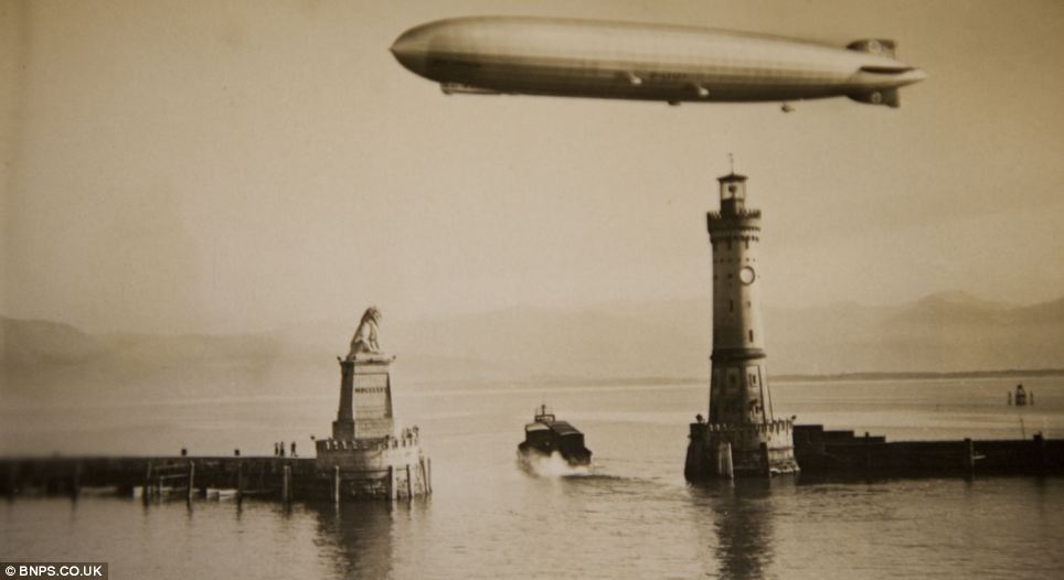 Reflected glory: A shining Zeppelin flies over calm waters at Lindau harbour in Bavaria in one of the amazing photographs