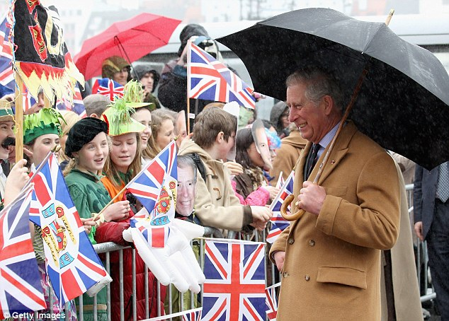 Charles laughs as he spots members of the crowd in Royal masks during the visit to Bryggen Wharf in Norway