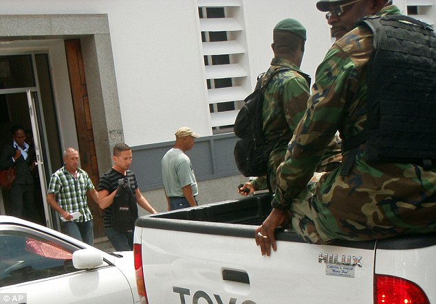 Mayer, 43, second from left, and Hart, 41, third from left, are escorted by police officers back to court following their arrest during a stop on a gay cruise of the Caribbean
