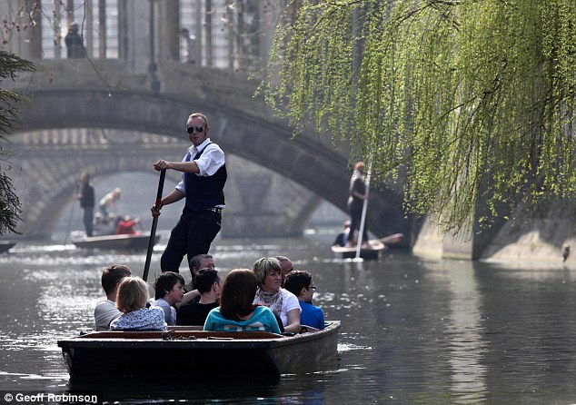 Taking a punt: Visitors enjoy the view of the River Cam in Cambridge in one of the traditional boats