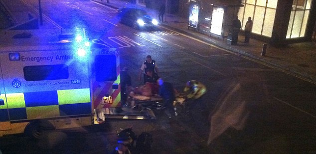 Gun blast: German Gorbuntsov is pictured here being carried into ambulance after being shot in Canary Wharf
