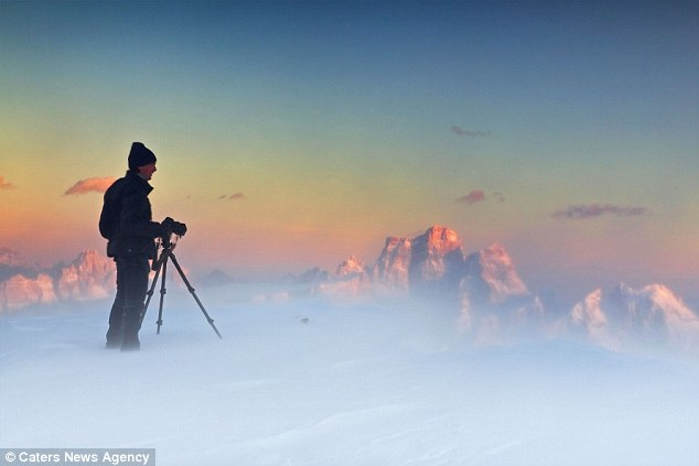 Walking on air: Snow whipped up by fierce winds gives the impression that photographer Matteo Zanvettor is standing in the clouds
