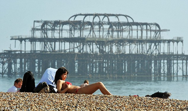 A sunbather relaxes in a red bikini on Brighton Beach with the burned out shell of the pier in the background