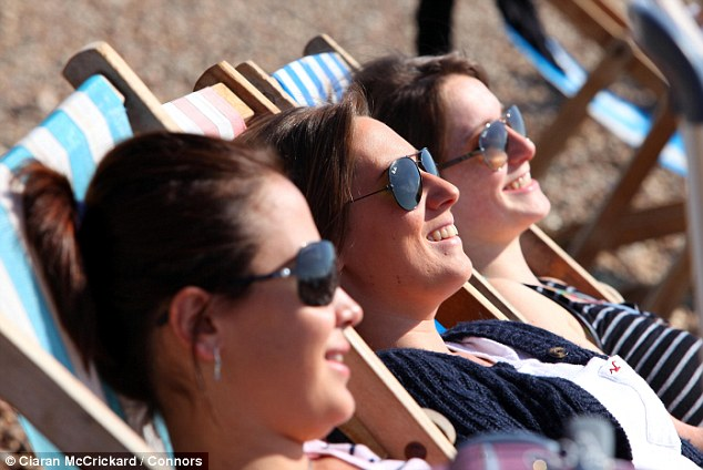 Cooling off: Hundreds of people flocked to Brighton beach to soak up the sun today, including Londoners Rania Nafissah, left, Jessica Pearcey, centre, and Kym Shaen-Carter