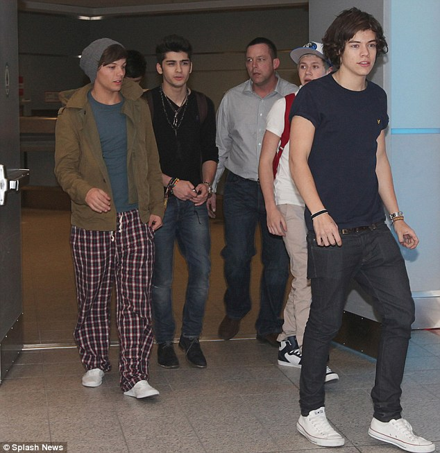 Feeling the strain? The boys were later seen arriving at Toronto airport looking slightly bleary-eyed, with Louis even appearing to be wearing pyjama bottoms
