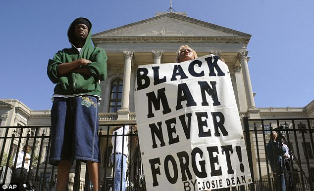 Widespread protests:  Maurice Collier (L) and Josie Dean stand in protest before students from historically black colleges in Atlanta arrive at the Georgia capitol to protest the shooting