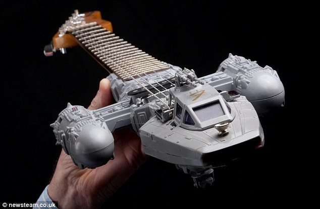 May the chords be with you: Tom Bingham shows off one of his painstakingly made Star Wars guitars, this one in the shape of the Anakin Jedi Starfighter