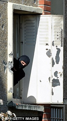Siege: A hooded policeman looks out of a window at the bullet-ridden apartment where Merah made his last stand. The killer's father claims police could have taken him alive