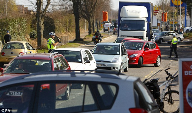 Chaos: Prompted by ministers to fill their tanks, motorists besieged garages and lengthy queues formed around the country yesterday. Community Support Officers manage the traffic queuing outside a Total service station in Christchurch, Dorset