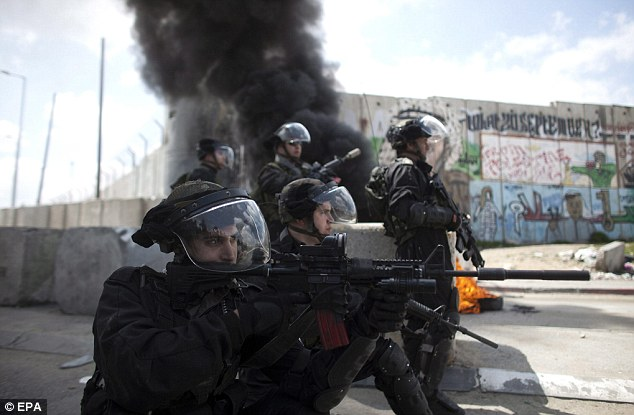 Taking positions: Israeli border policemen next to a part of the separation wall between Israel and Palestine during clashes at the Kalandia checkpoint today