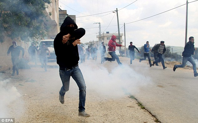 Running for cover: Palestinian protesters scatter rom tear-gas fired by Israeli soldiers