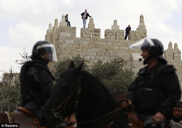 Mounted: Israeli border police stand guard as Palestinians watch clashes from a wall after Friday prayers outside Damascus Gate
