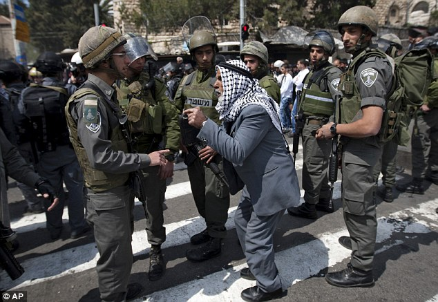 At odds: An elderly Palestinian man argues with Israeli border police officers outside Damascus Gate in Jerusalem's Old City