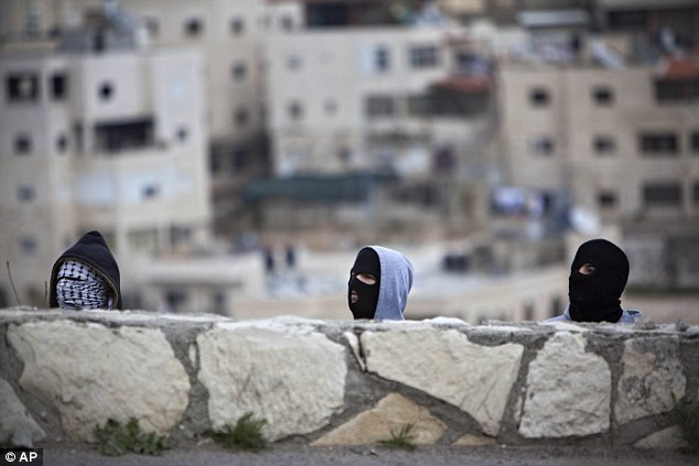 Risky business: Masked Palestinians take cover during clashes with Israeli troops