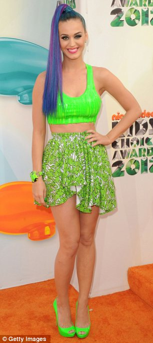 Two different pictures: Selena Gomez looked elegant in her daring two-piece outfit, while Katy Perry tried to avoid being slimed in her bright green attire at tonight's Nickelodeon Kid's Choice Awards