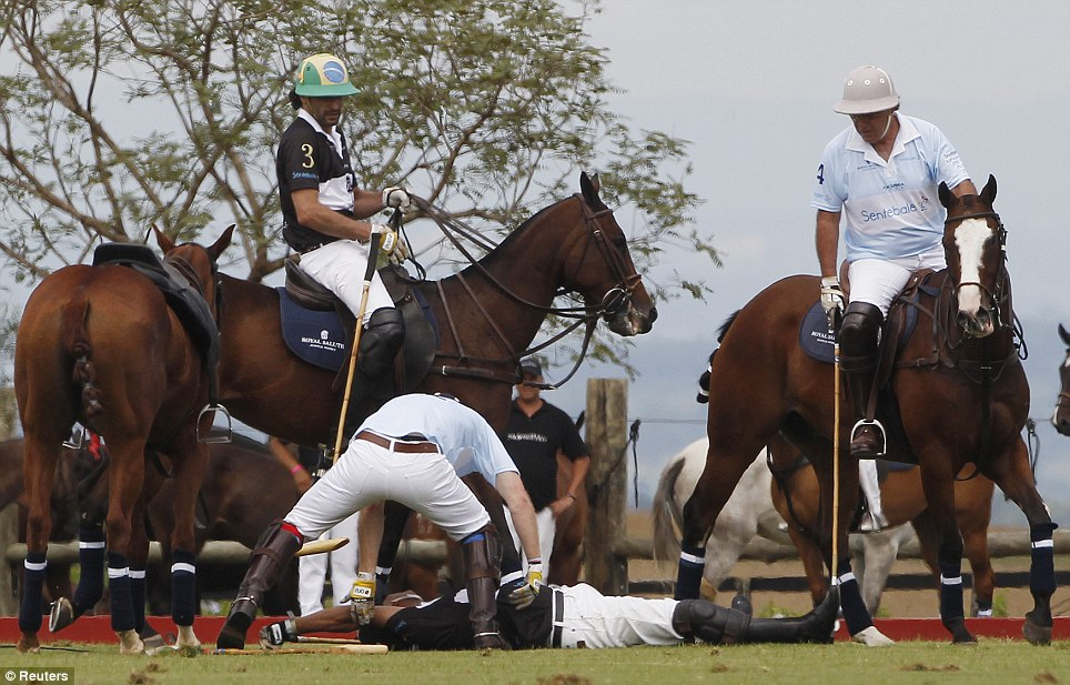 Quick-thinking: Prince Harry rushes to the rescue of Bash Kazi after the U.S. businessman was knocked unconscious after colliding with another rider during a polo match in Campinas, Brazil