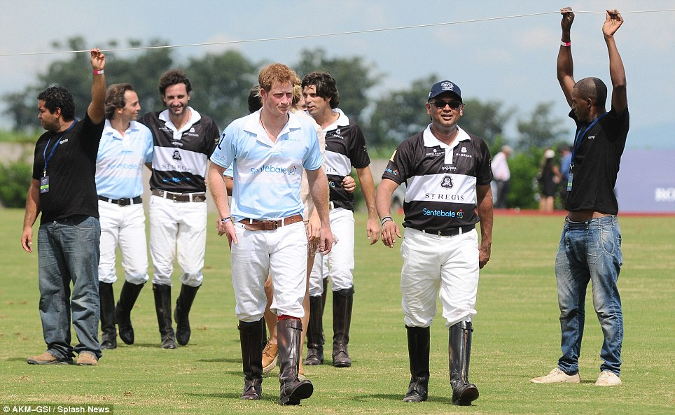 He's all right: Mr Kazi leaves the polo pitch with the prince by his side after the accident