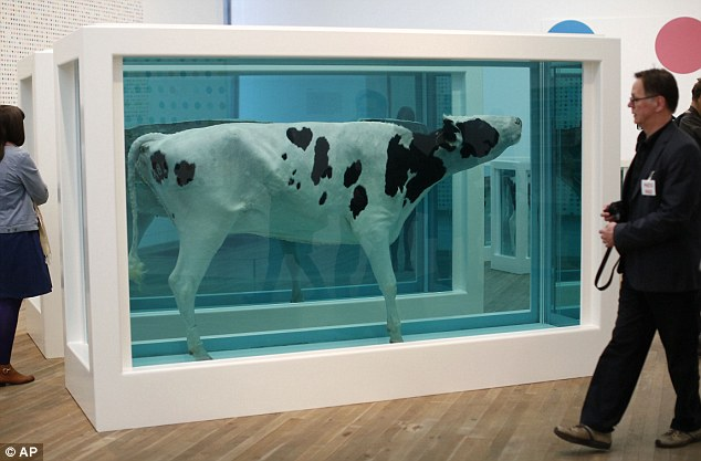 Controversial art on display: Hirst's 2007 exhibition piece 'Mother and Child Divided', composed of a cow and a calf sliced in half in glass tanks of formaldehyde