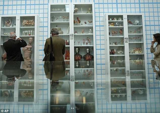 Visitors are reflected as they look at the 'Trinity - Pharmacology, Physiology, Pathology' display