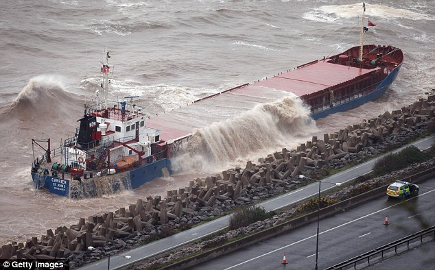 Waves pour over the side of the grounded cargo ship 'Carrier' as it lays against the sea defences