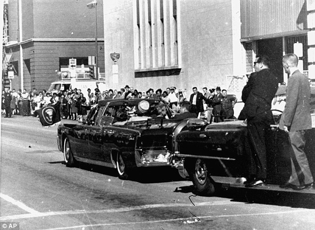 On the lookout: Hill, dressed in black and sunglasses, can be seen standing on a vehicle's running board as President Kennedy drives through the streets of Dallas, Texas before the shooting