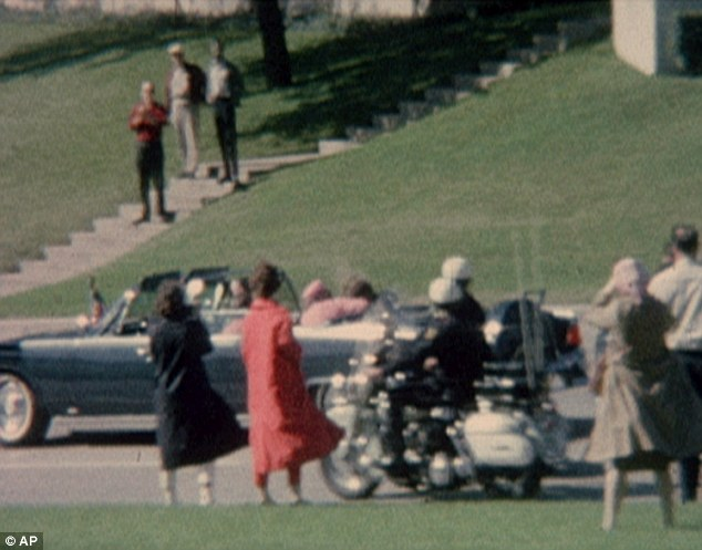 Fears: Mrs Kennedy, dressed in pink, cradles her husband seconds after he was shot. 'Jack, Jack, what have they done to you?' Hill remembers her saying on the way to hospital