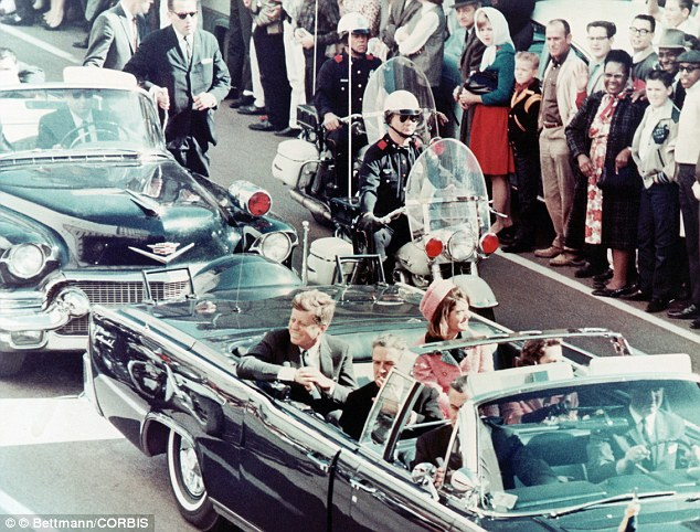 Unaware: President JFK and his wife Jackie riding in the motorcade before he was shot. Hill is standing top left