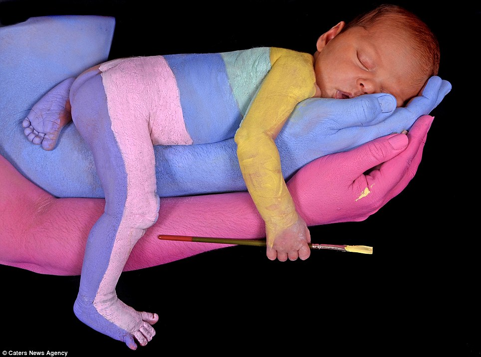 Craig Tracy's youngest model: A baby takes a nap after being painted in different coloured stripes with paint suitable for human skin