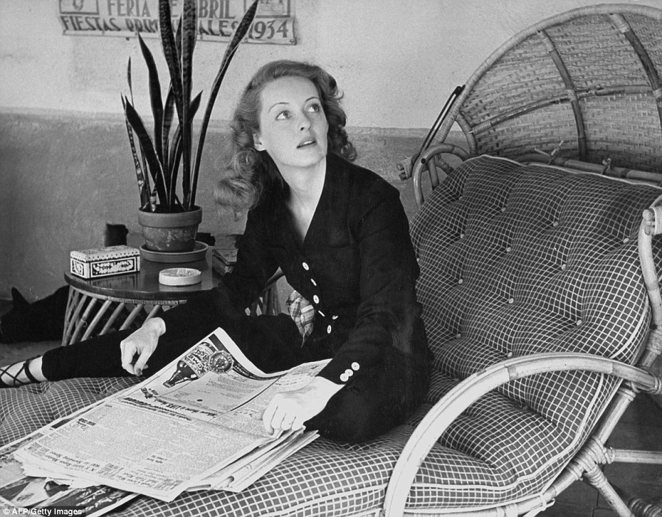 At home: Actress Bette Davis skims through the morning papers in a series of never seen photographs taken by Alfred Eisenstaedt in 1939 and released by LIFE on what would be the star's 104th birthday