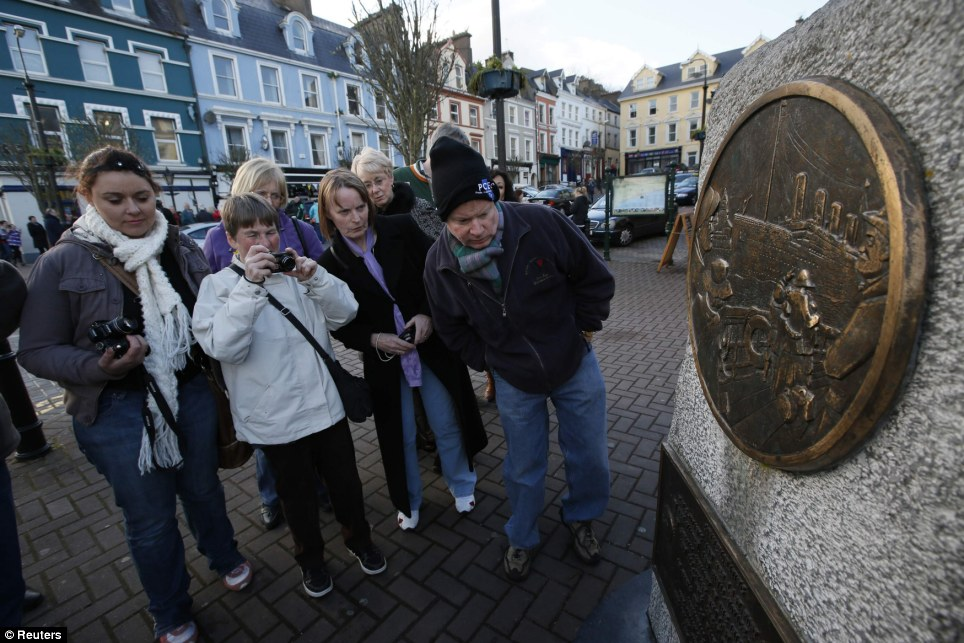 Tour: Passengers from the Titanic Memorial Cruise view a Titanic plaque while on a tour of Cobh