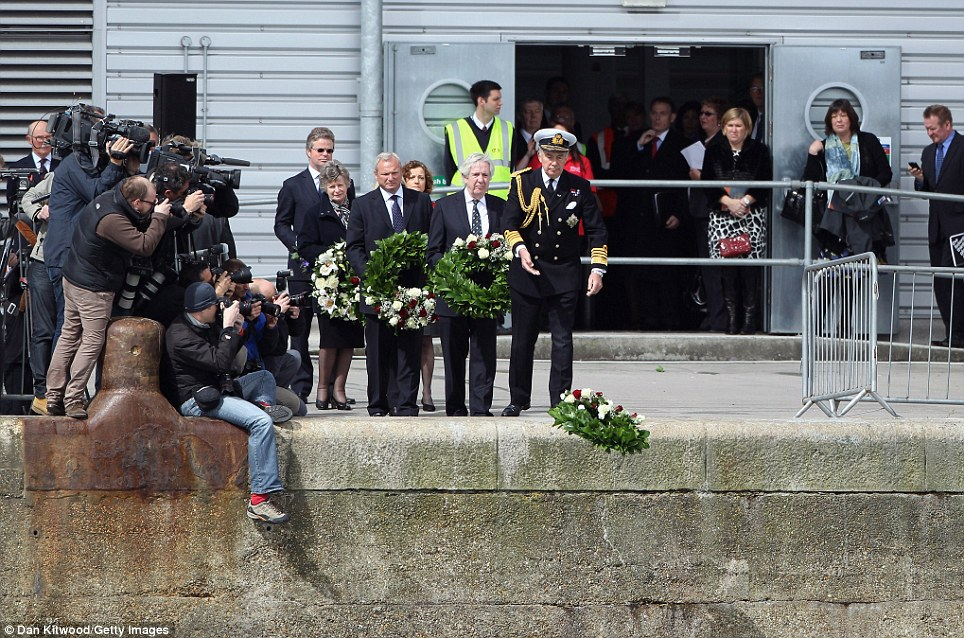 Sombre: Local dignitaries also joined the memorial in Southampton, throwing their own wreaths off the dockside in the south coast city today