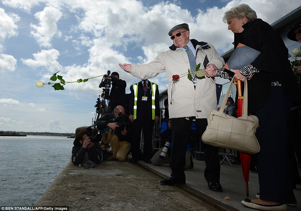 Emotional: A man throws a single white rose into the sea at berths 43/44 from the where the Titanic set sail, during a memorial service in Southampton 100 years to the day after it set off on its maiden voyage