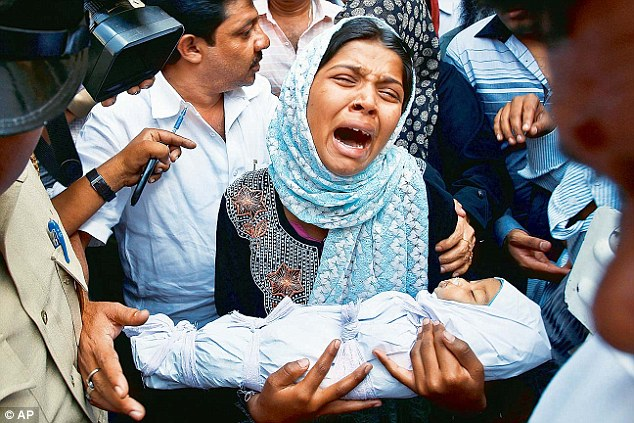 Devastated: Mother Reshma Bano wails as she holds the body of her three-month-old daughter Neha Afreen outside a hospital morgue in Bangalore