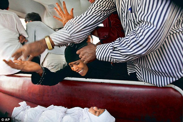 Heartbroken: A relative cries over the body of three-month-old Neha Afreen after she died from injuries allegedly inflicted by her father