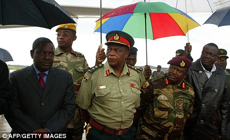 Business as usual: Zimbabwean security and officials watch as the president arrives from Singapore following a two-week absence, which sparked reports that he was battling for life in the Asian city-state