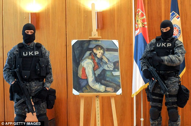 Under surveillance: Armed policemen guard the painting during a news conference today