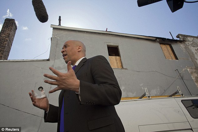 Fire: Booker stands outside the boarded up house which was earlier engulfed by flames