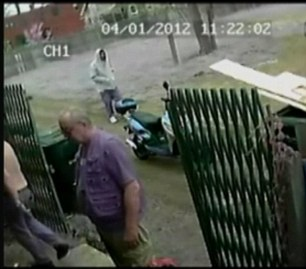 Man in grey hoodie walks past the moped