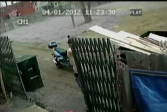 Courageous: From behind a gate Mr Gramza can just be seen firing off six shots at the hapless robber as he makes his getaway, without the moped