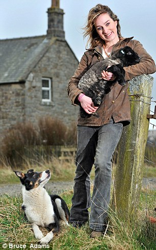 Flock star: Emma, cradling one of her lambs, watched by sheepdog Alfie, found it difficult to meet someone as like-minded