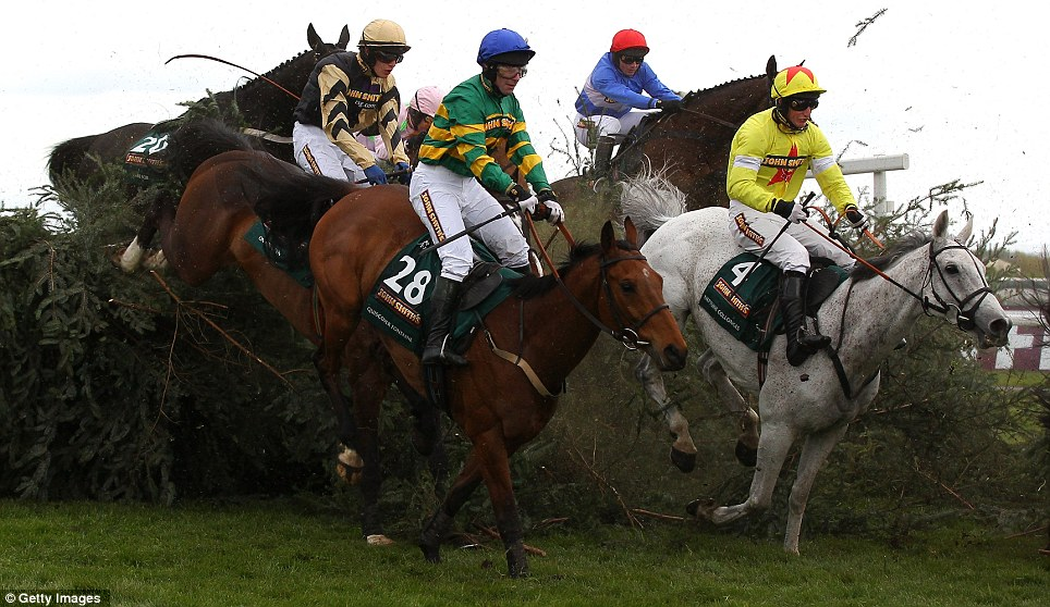 Neptune Collonges, right, pulls clear of the pack as he comes down off the final fence