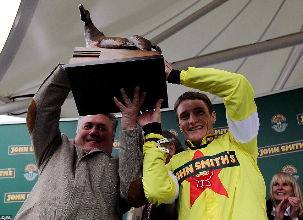 Elated: Trainer Paul Nicholls and jockey Daryl Jacob celebrate therr victory in the John Smith's Grand National Chase