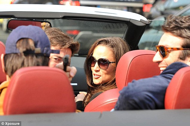 Negative image: Pippa smiles as her driver points what appears to be a pistol directly at a photographer during her last visit to Paris